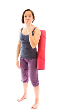 Young woman carrying exercise mat with hand over her mouth and shock photo