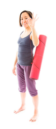Young woman carrying exercise mat showing ok sign photo