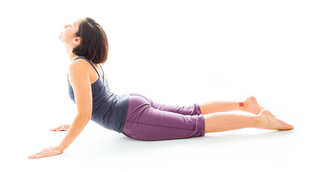 Young woman practicing yoga in cobra pose photo