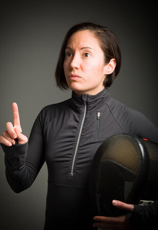 Female fencer pointing her finger up