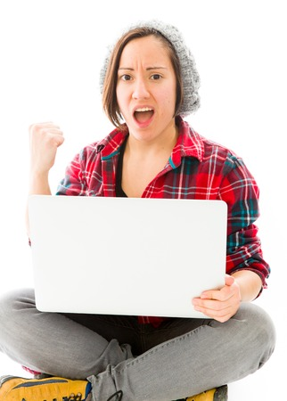 Young woman celebrating with using laptop