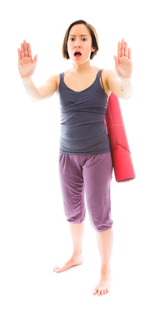 Young woman making stop gesture sign with carrying exercise mat photo