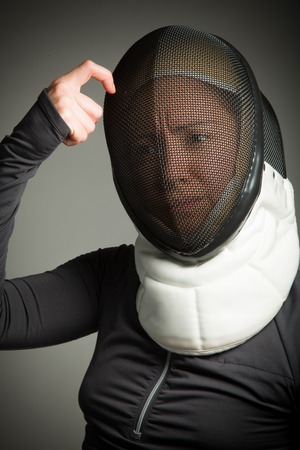 Close up of a female fencer in fencing mask with scratching head photo