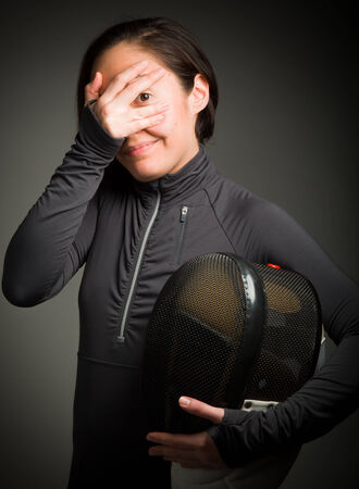 Female fencer peeking through hands covering face