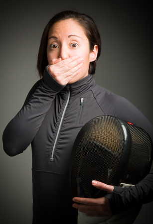 Female fencer hand over her mouth and shock Stock Photo
