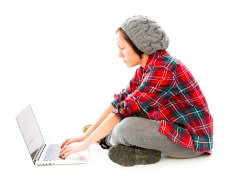 sitting on the ground: Young woman sitting on ground using laptop