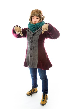 Young woman in warm clothing and showing thumbs down sign with both hands Stockfoto