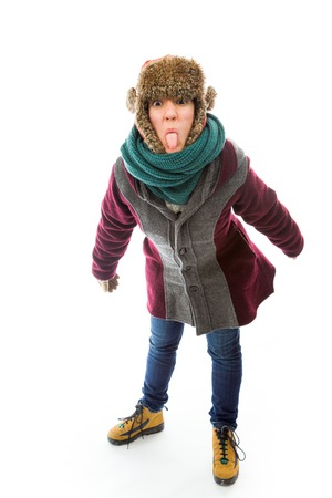 Young woman in warm clothing and sticking out her tongue photo