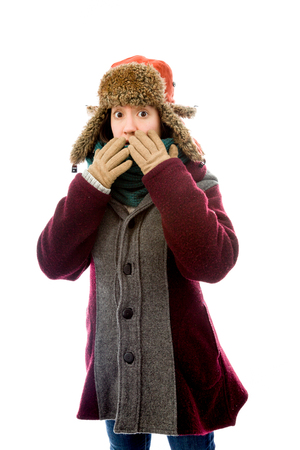 Young woman in warm clothing and looking shocked