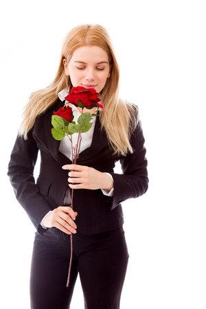 Businesswoman smelling a red rose flower