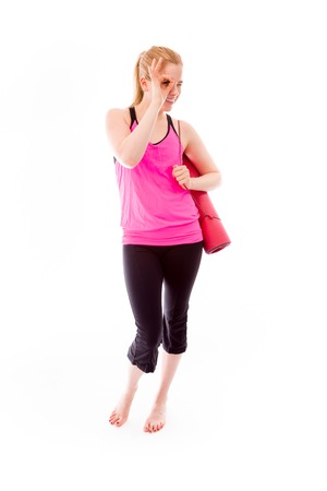 Young woman carrying exercising mat using fingers as glasses photo