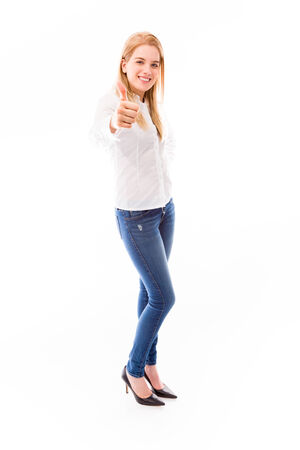 Young woman standing and showing thumbs up sign photo