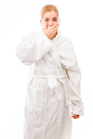Young woman standing in bathrobe with hand over her mouth photo