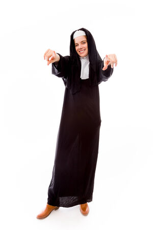religious habit: Young nun pointing towards camera from both hands Stock Photo
