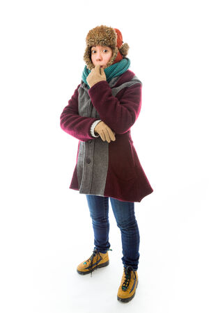 Scared young woman in warm clothing biting her fingernails photo