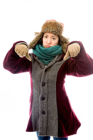 Young woman in warm clothing and showing thumbs down sign with both hands photo