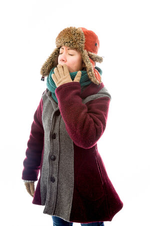 Young woman in warm clothing and yawning photo