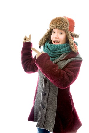 Young woman in warm clothing and pointing back