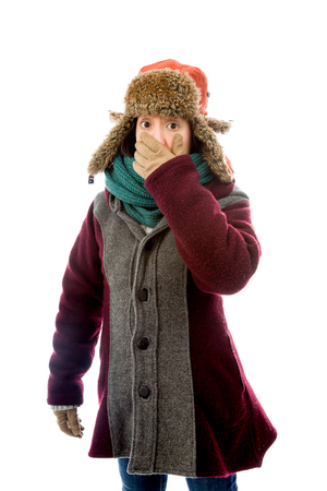 Young woman in warm clothing with hand over mouth photo