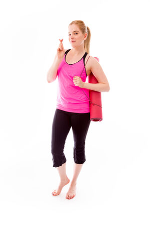 Young woman carrying exercising mat wishing with crossing fingers photo