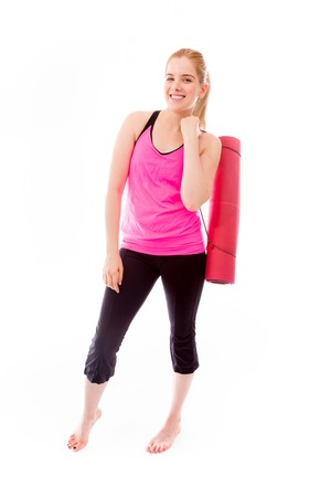 sanctification: Young woman carrying exercise mat smiling Stock Photo