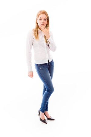Young woman standing and looking shocked photo