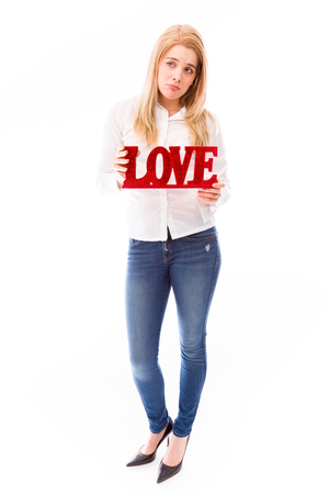 Romantic young woman in love shot in studio isolated on a background photo