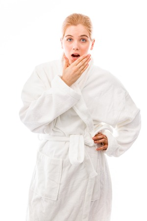 Young woman standing in bathrobe and looking shocked photo