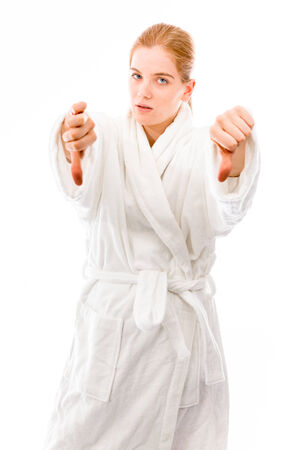 Young woman standing in bathrobe showing thumbs down sign with both hands photo