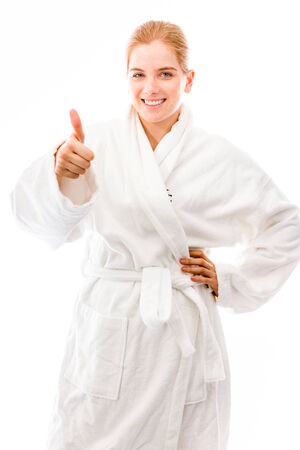 Young woman standing in bathrobe and showing thumbs up towards camera photo