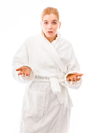 Young woman standing in bathrobe and dont know what to do isolated on white background photo