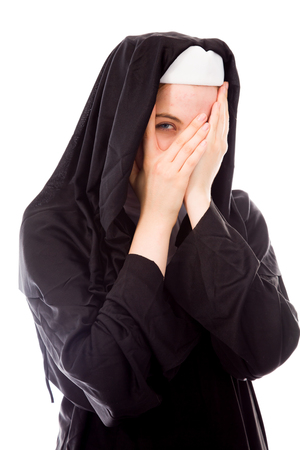 religious habit: Young nun peeking through hands covering face