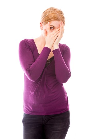 hands covering face: Young woman peeking through hands covering face Stock Photo