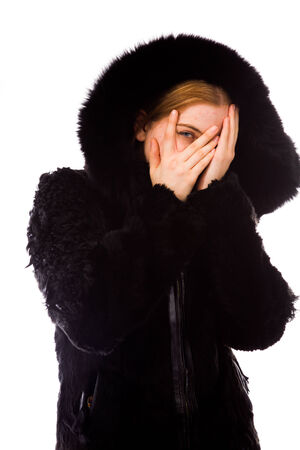 Young woman peeking through hands covering face photo