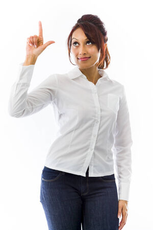 finger tip: Indian young woman pointing upwards and looking at tip of finger