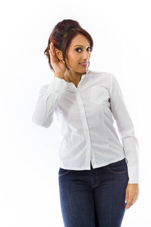 Indian young woman with hand to ear listening isolated over white background photo
