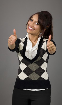 cocked: Indian businesswoman showing thumbs up from both hands isolated on colored background