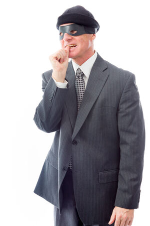 Businessman wearing eye mask and standing with finger in mouth photo