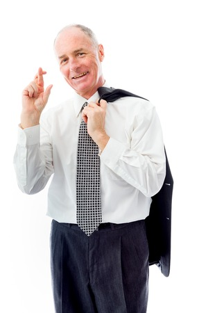 Businessman standing with finger crossed for luck photo