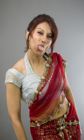 cocked: Young Indian woman sticking out her tongue Stock Photo