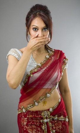 Young Indian woman with hand over her mouth