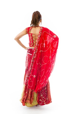 arms akimbo: Rear view of a young Indian woman standing with her arms akimbo