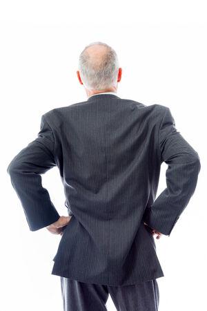mani sui fianchi: Vista posteriore di un uomo d'affari in piedi con le braccia akimbo Archivio Fotografico