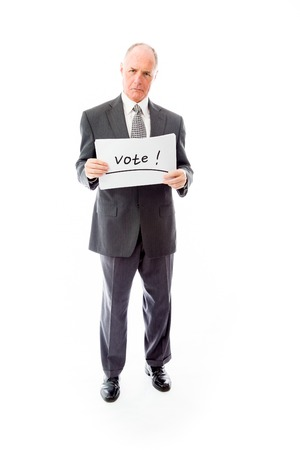Businessman holding a message board with the text words Vote photo