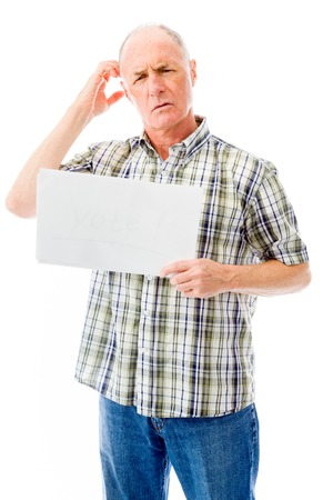 Senior man holding a blank placard and scratching his head photo