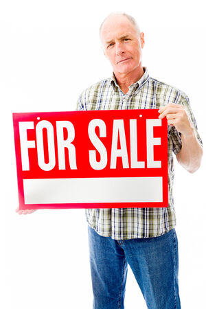 Senior man showing a for sale sign photo