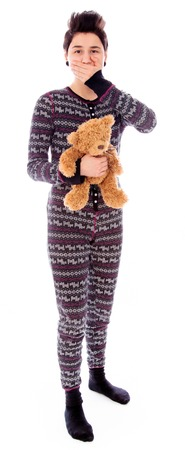 Young woman holding teddy bear with hand over her mouth