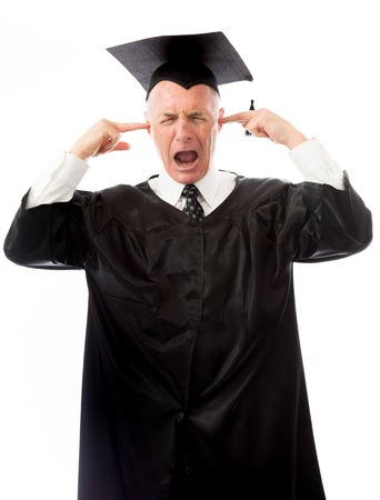 Senior male graduate crying with fingers in ears