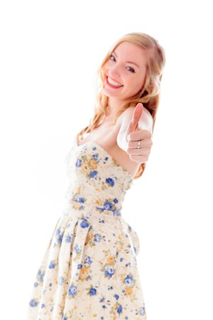 Beautiful young woman standing and showing thumbs up sign photo
