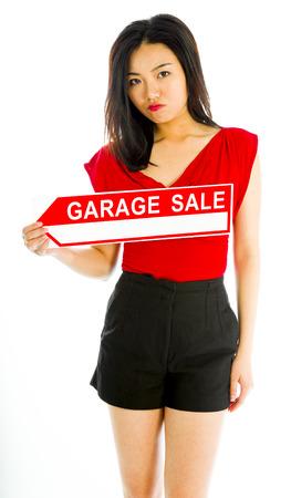 英文ガレージ セール ポスターを保持している店員